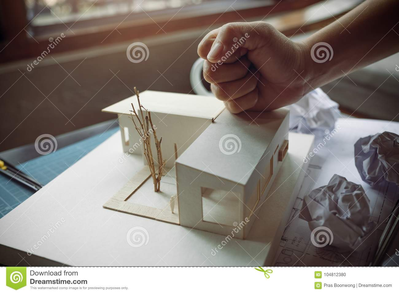 Closeup image of an angry architects try to destroy an architecture model on the table