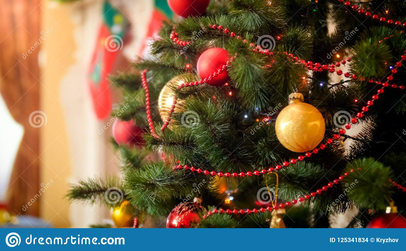 Closeup image of colorful lights glowing on adorned Christmas tree at house
