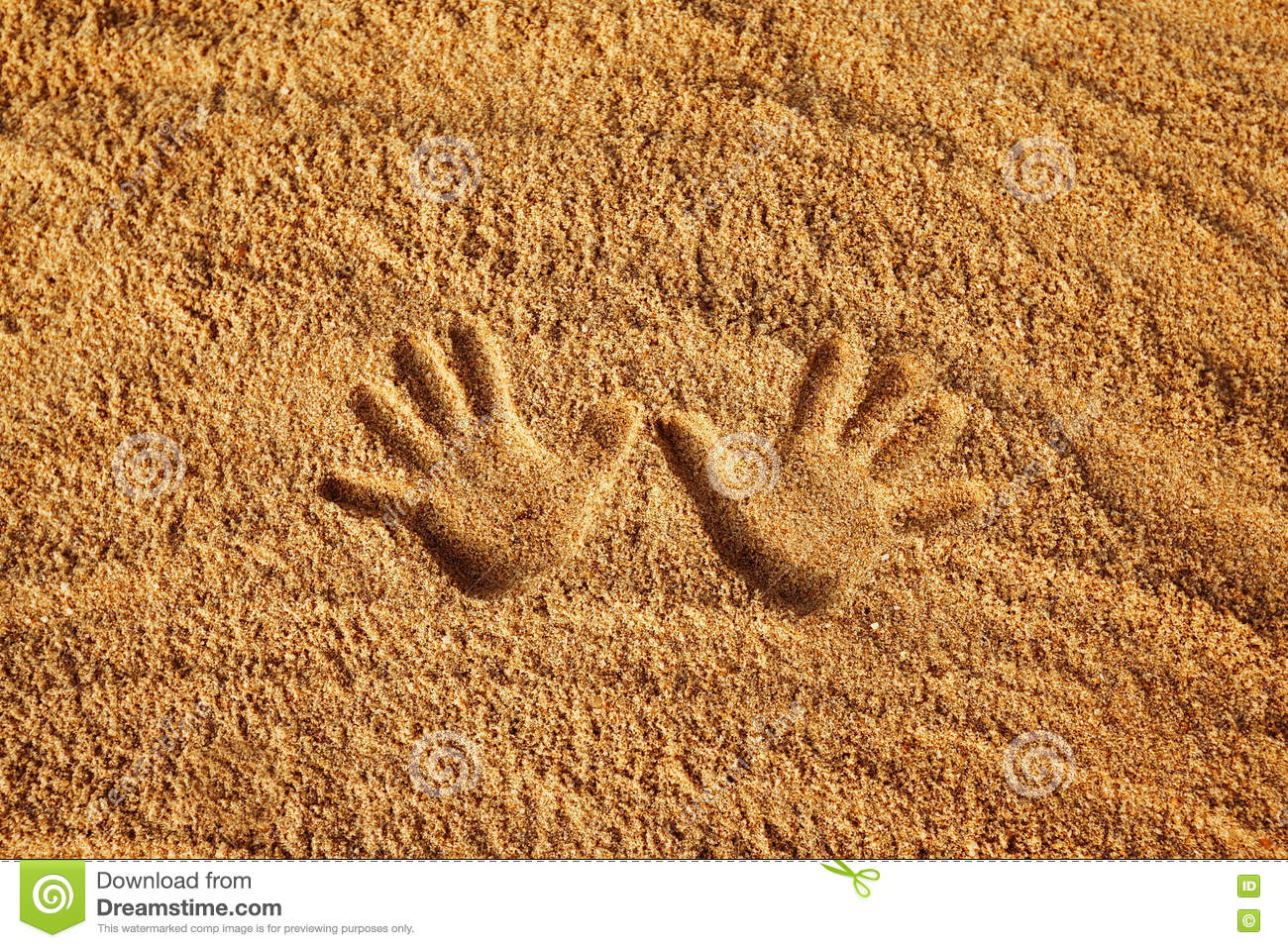 Closeup image of hand prints on yellow textured sand background