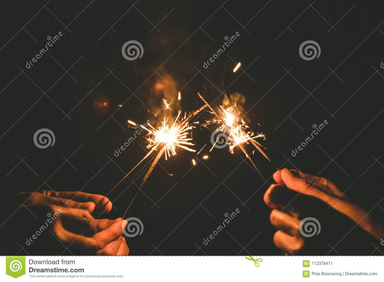 Hands holding sparklers for celebrate in the night time