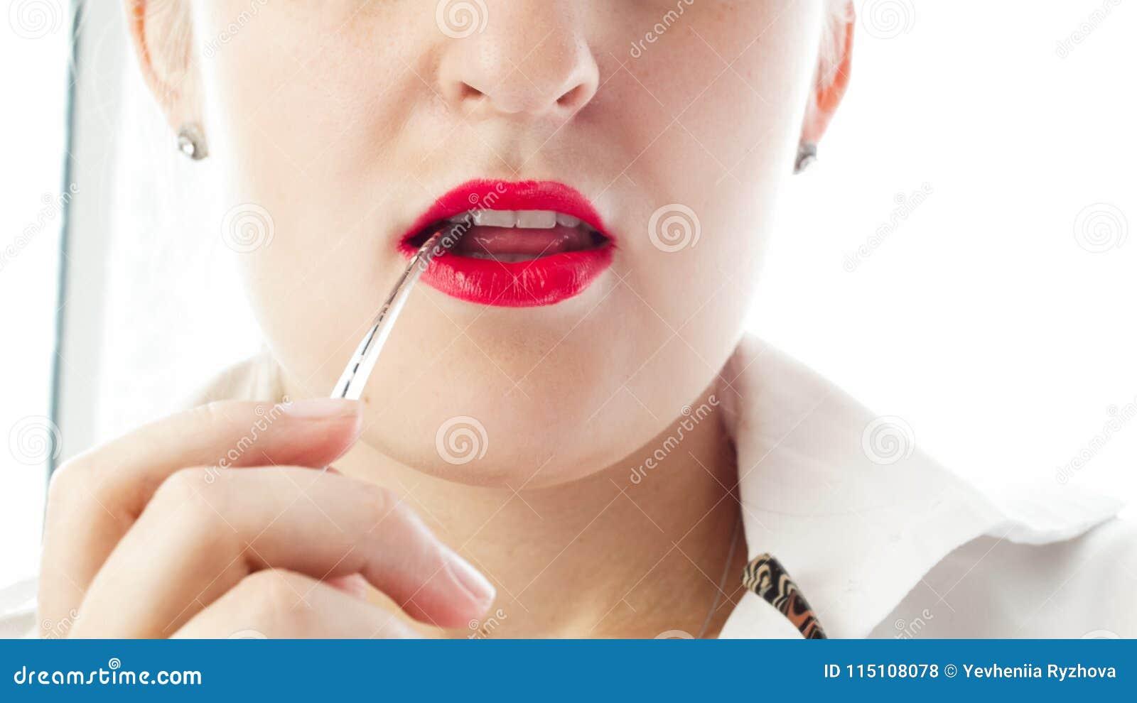 Closeup image of young woman biting eyeglasses earpiece