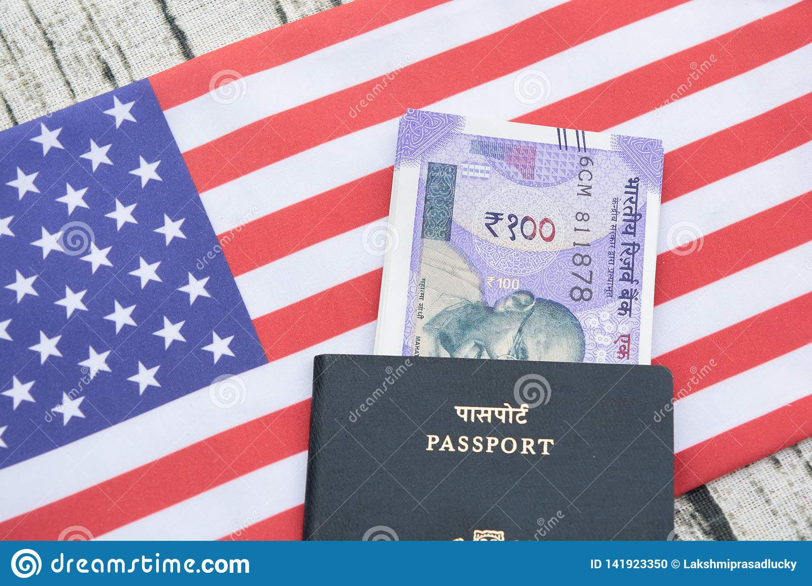 Closeup of Indian passport with currency on USA or america`s flag as a background