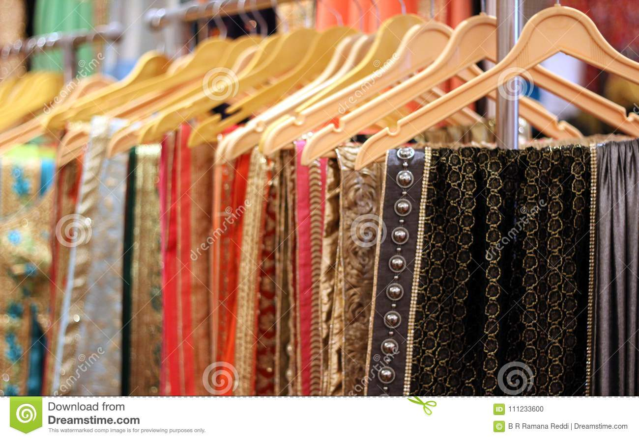 a5977aff8e Closeup of Indian woman clothes Sarees or Saris on hangers in display of a  retail shop or store