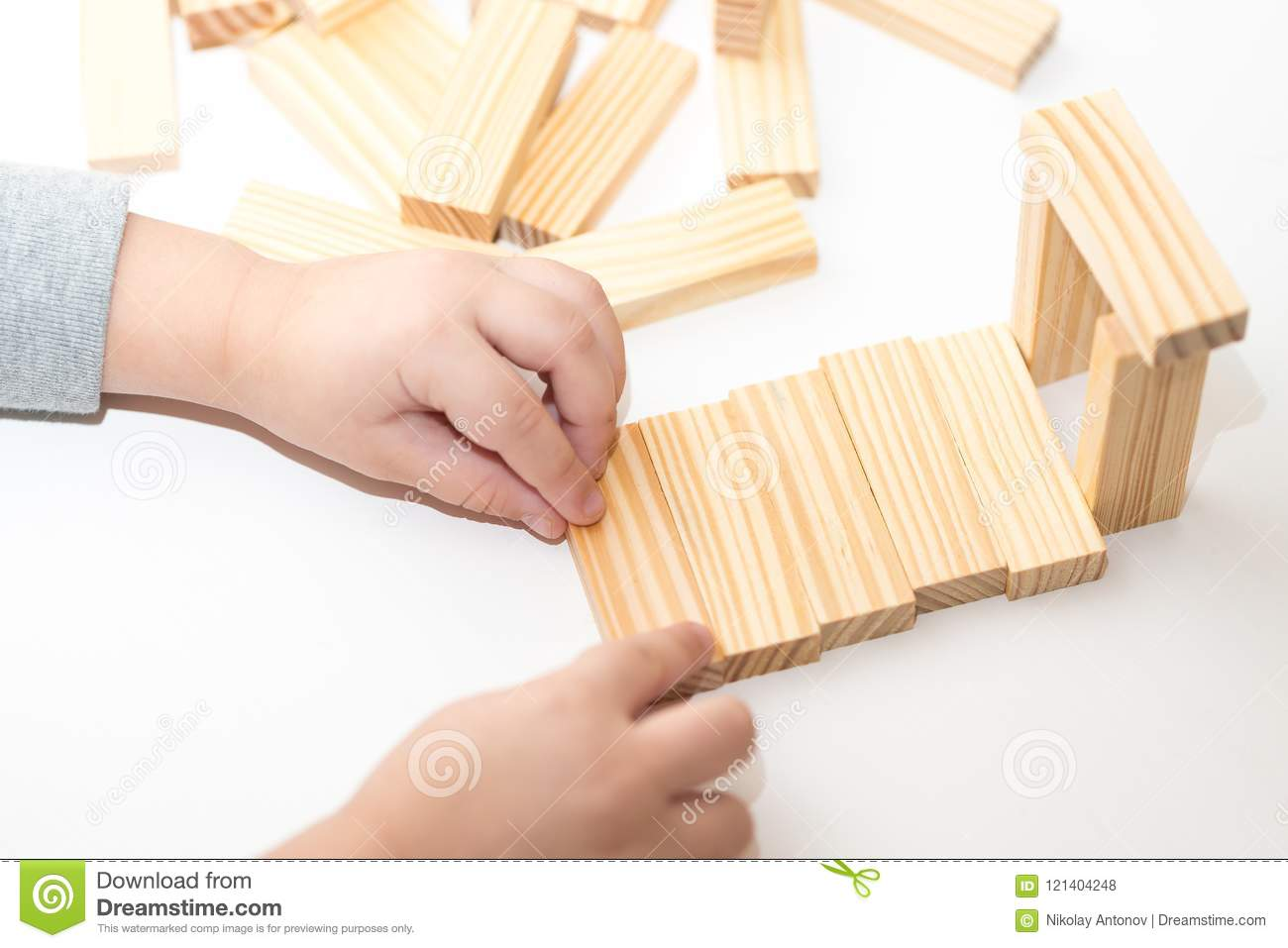 Closeup of kids hands playing with wooden blocks and building house. Education concept.