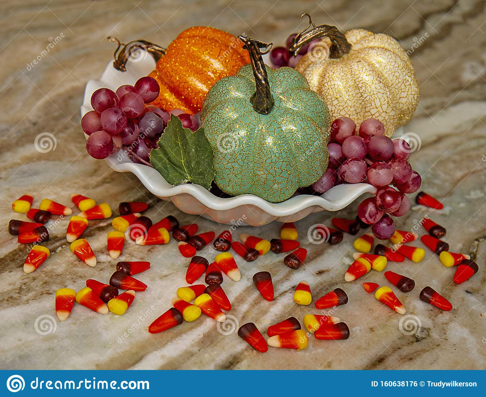Closeup Of Kitchen Counter With Three Faux Decorative Pumpkins Grapes And Candy Corn Scattered Around Base Stock Photo Image Decorations 160638176
