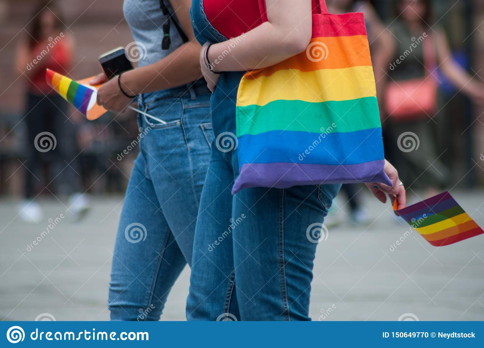Lesbian girls walking in the street with rainbow bag and rainbow flags before the gay pride