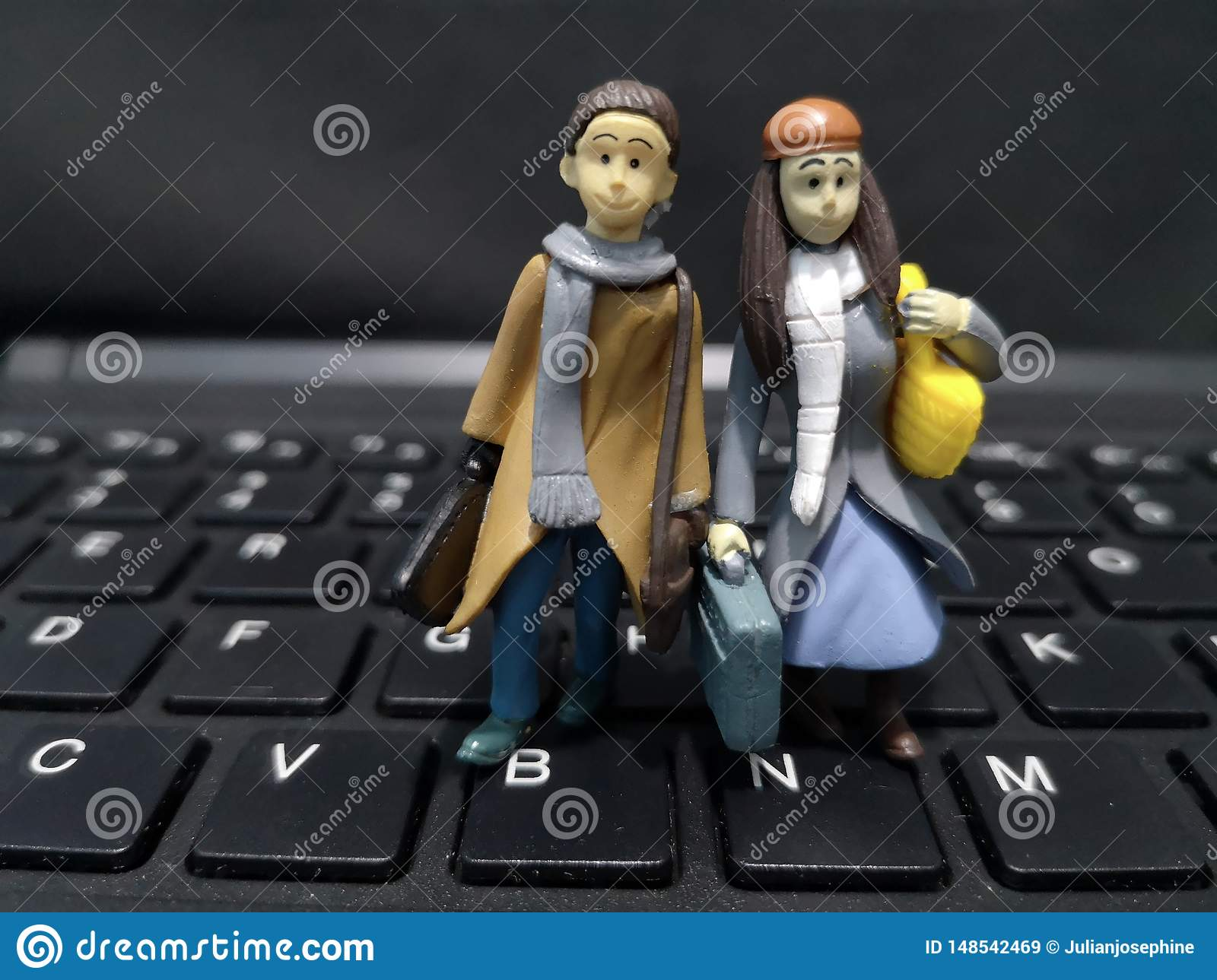 Closeup and macro shot of miniature working people with their suitcase and a computer background.