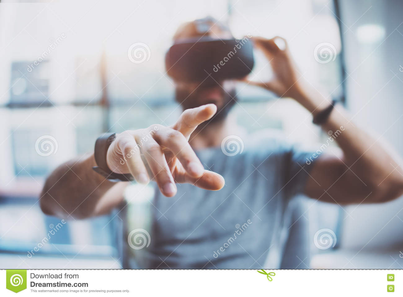 Closeup of male hand.Bearded young man wearing virtual reality goggles in modern coworking studio. Smartphone using with