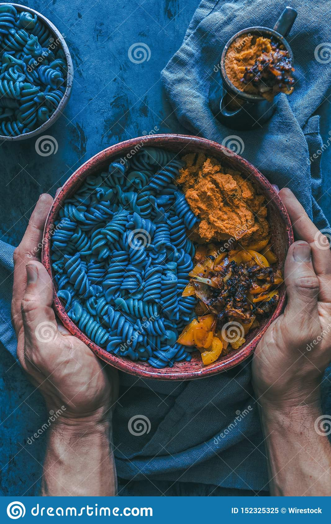 Closeup of a male holding a plate with vegan mermaid pasta in it