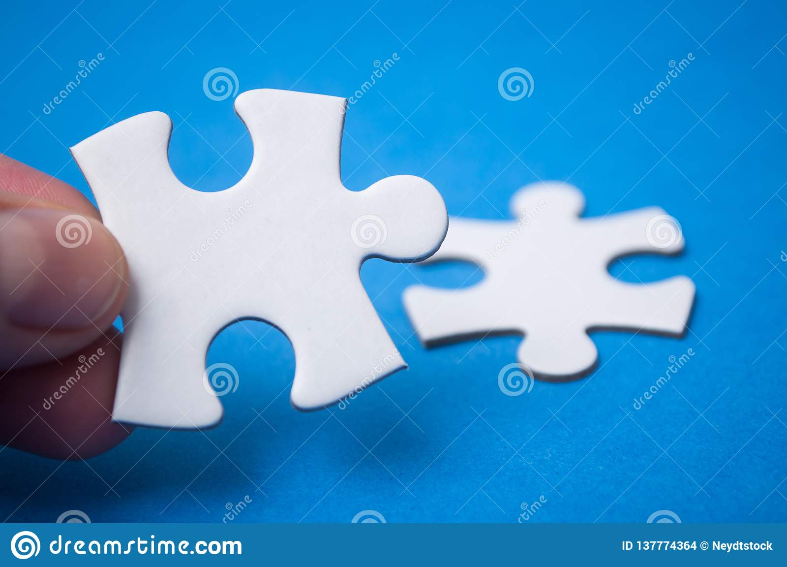 man connecting with hand two jigsaw puzzle pieces on blue background. The concept of finding the right solutions in