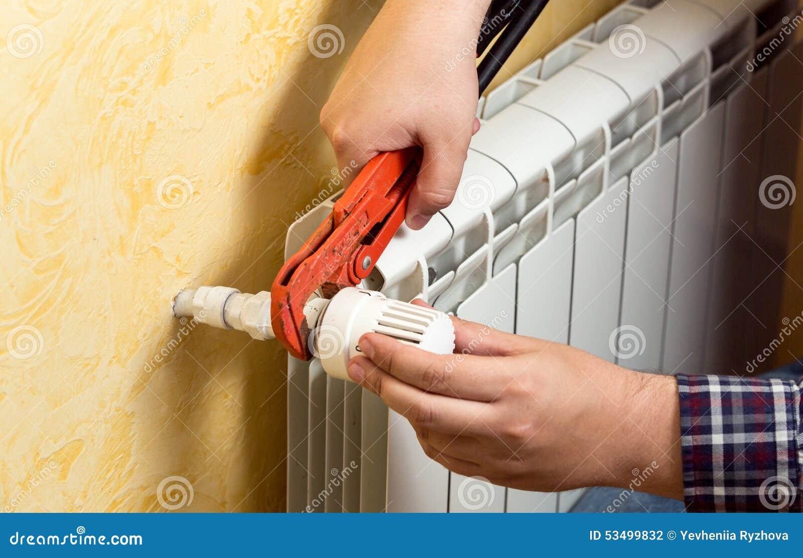 Closeup of man installing heating radiator and connecting valve