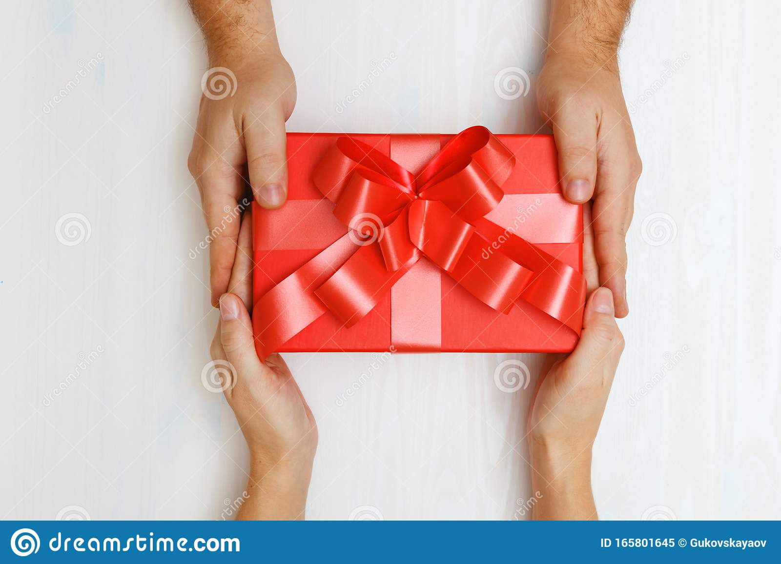 Homemande Christmas Gifts 2020 Closeup Of A Mans Hand Giving A Red Box With A Gift To A Woman
