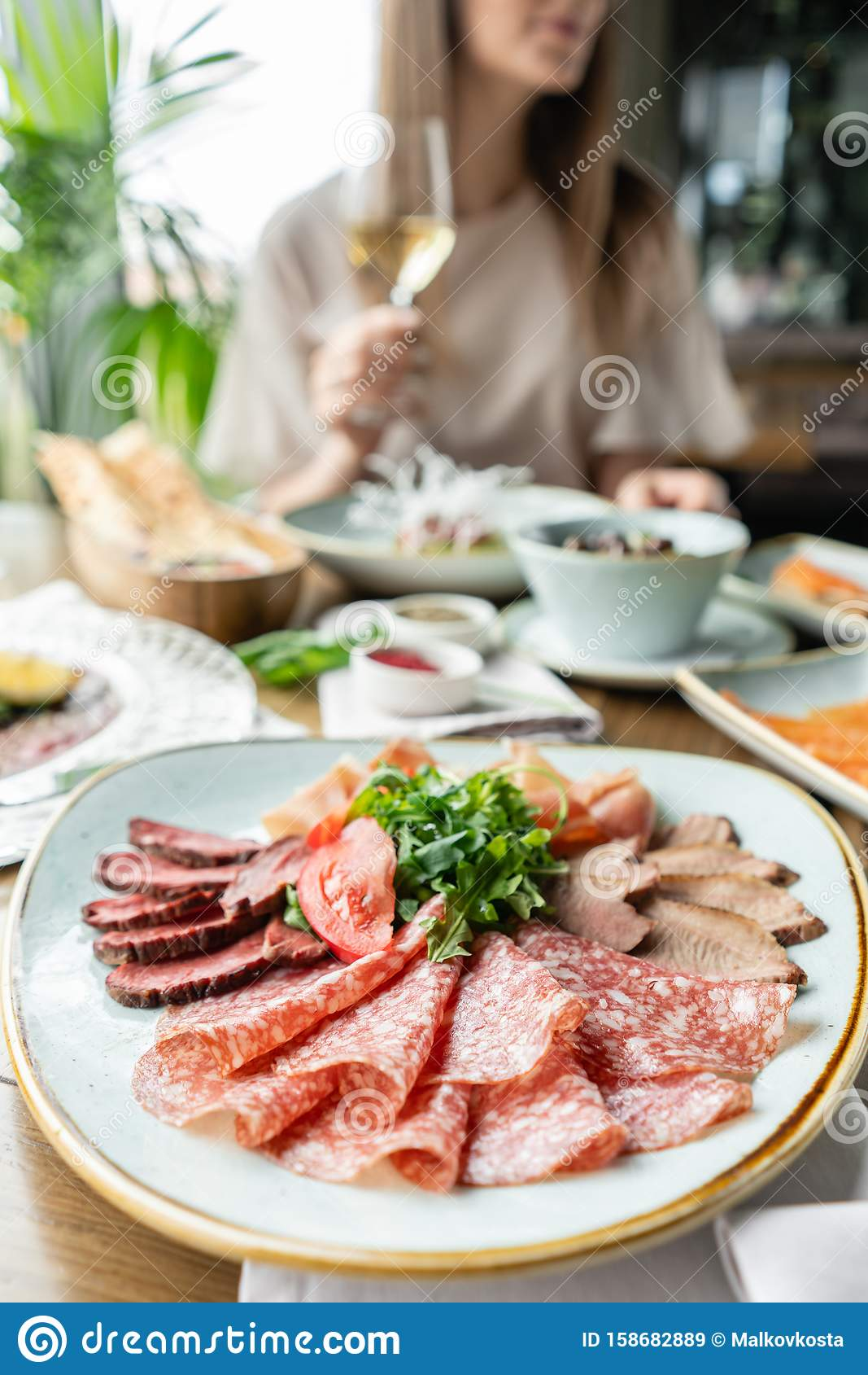 Closeup antipasti, salami, meat plate in the restaurant. Variety of dishes on the table. Italian cuisine