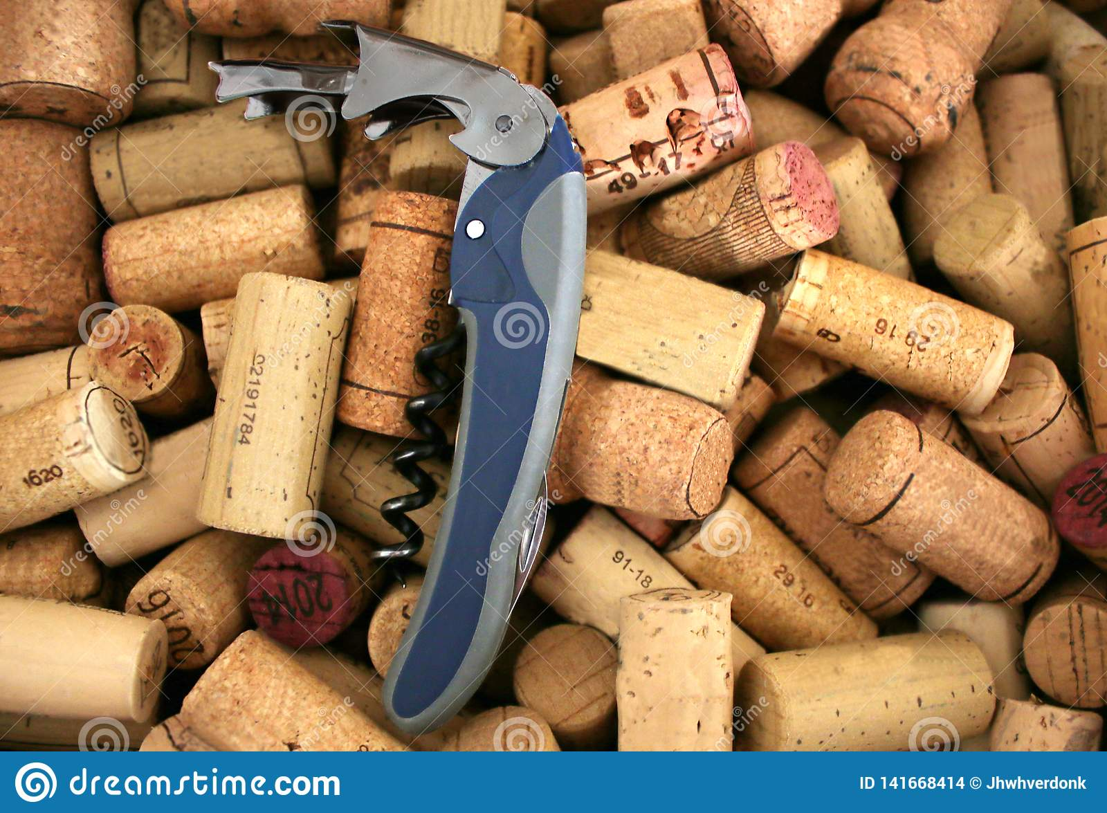 Closeup of a metal corkscrew in the midst of wooden corks