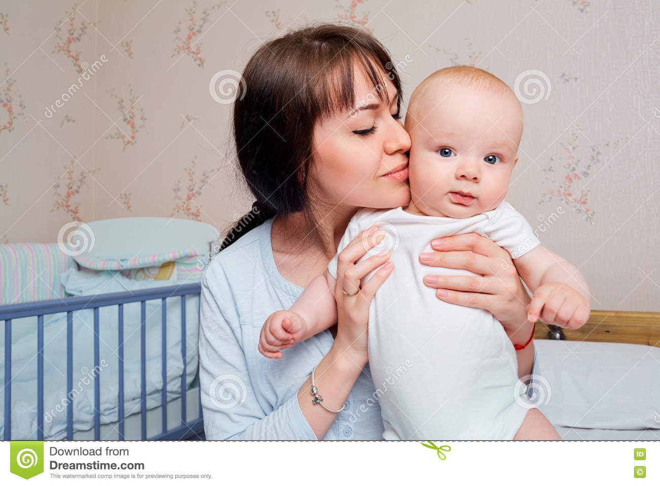 Baby bed next to mom - Mom Pajamas Tenderly Kisses The Baby Boy On The Bed In T