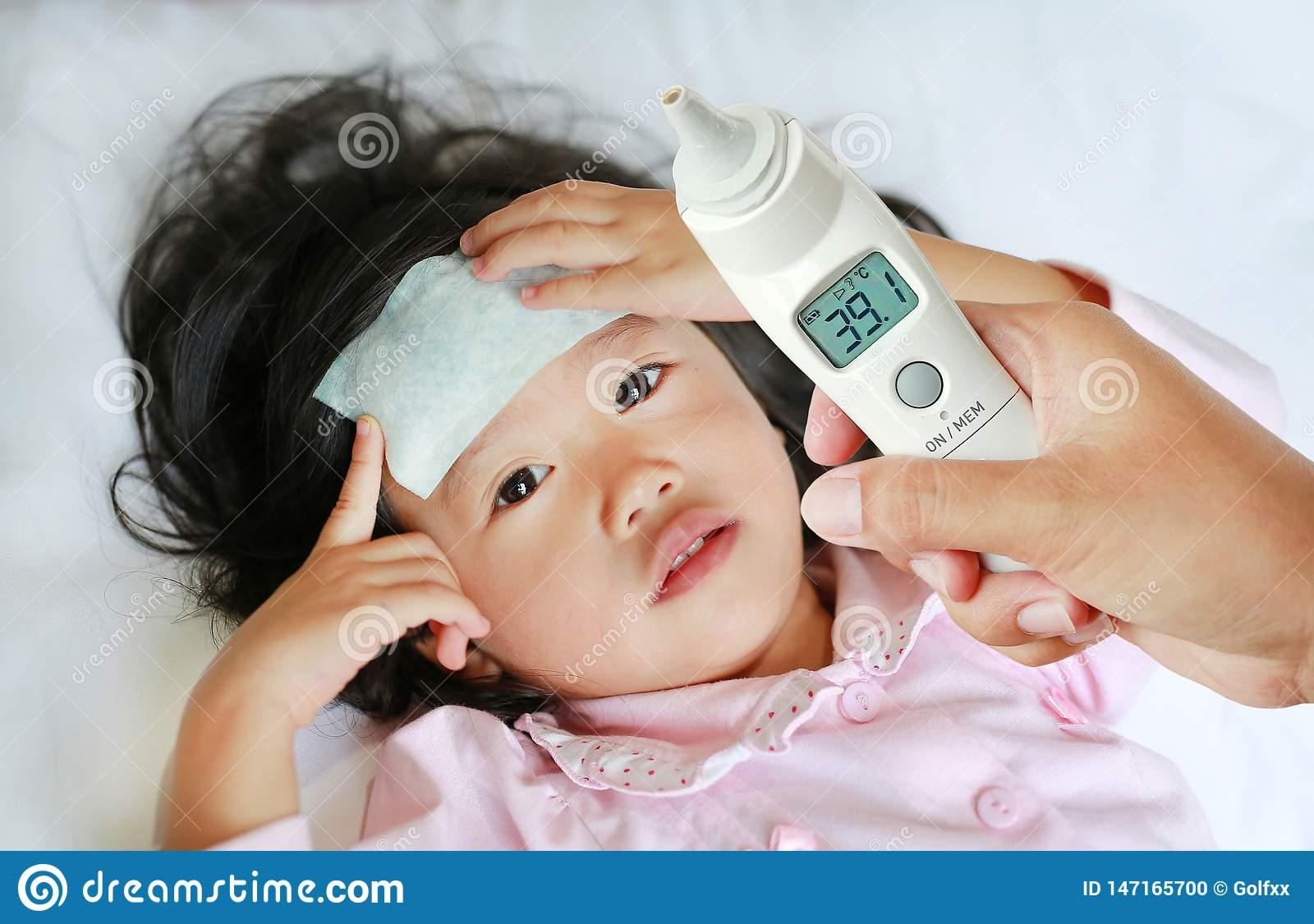 Closeup mother hand takes temperature for her daughter with ear thermometer on bed at home