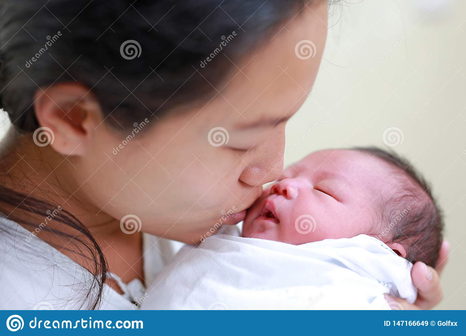 Closeup mother kissing infant baby in her arms in hospital after delivery room