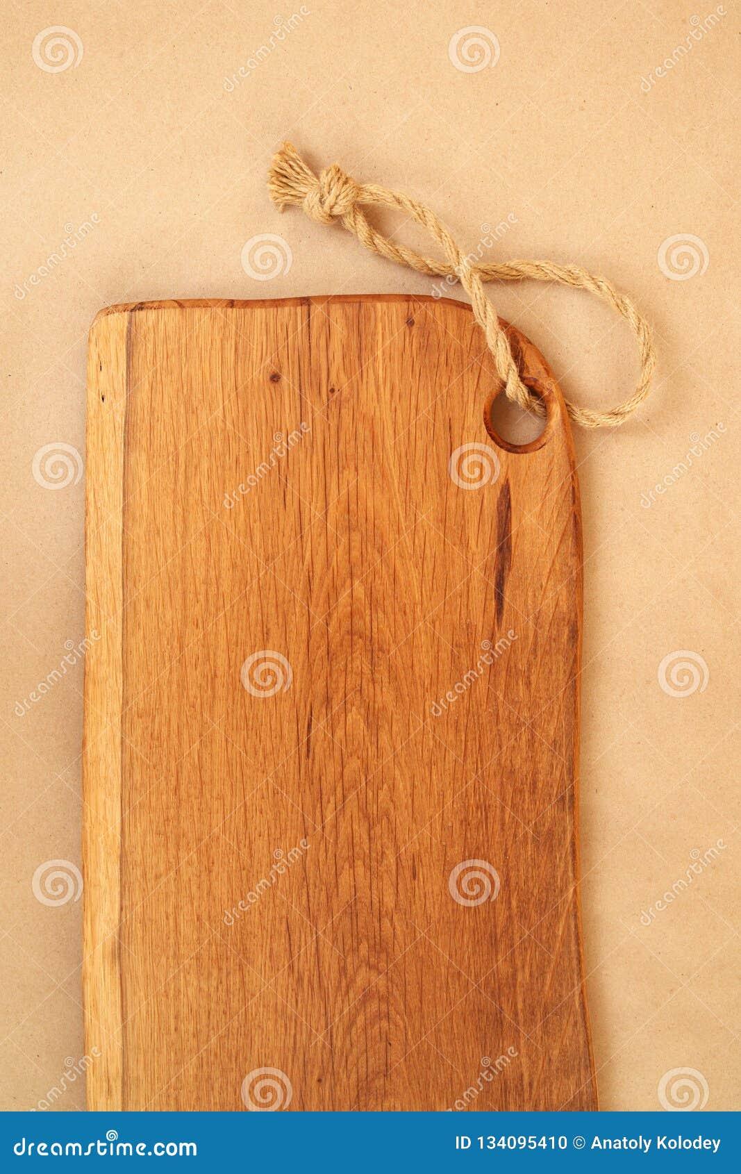 Closeup of oak chopping board on craft paper. Restaurant menu background. Rustic kitchen background & Closeup Of Oak Chopping Board On Craft Paper. Restaurant Menu ...