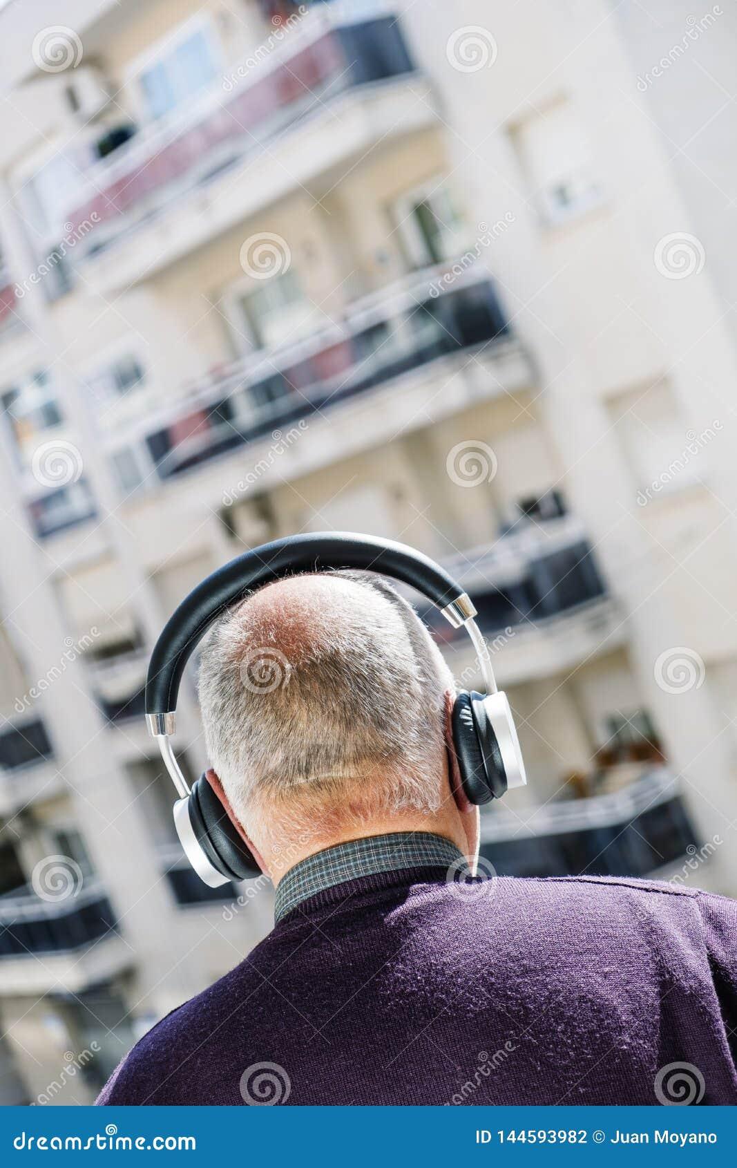 Old caucasian man using headphones