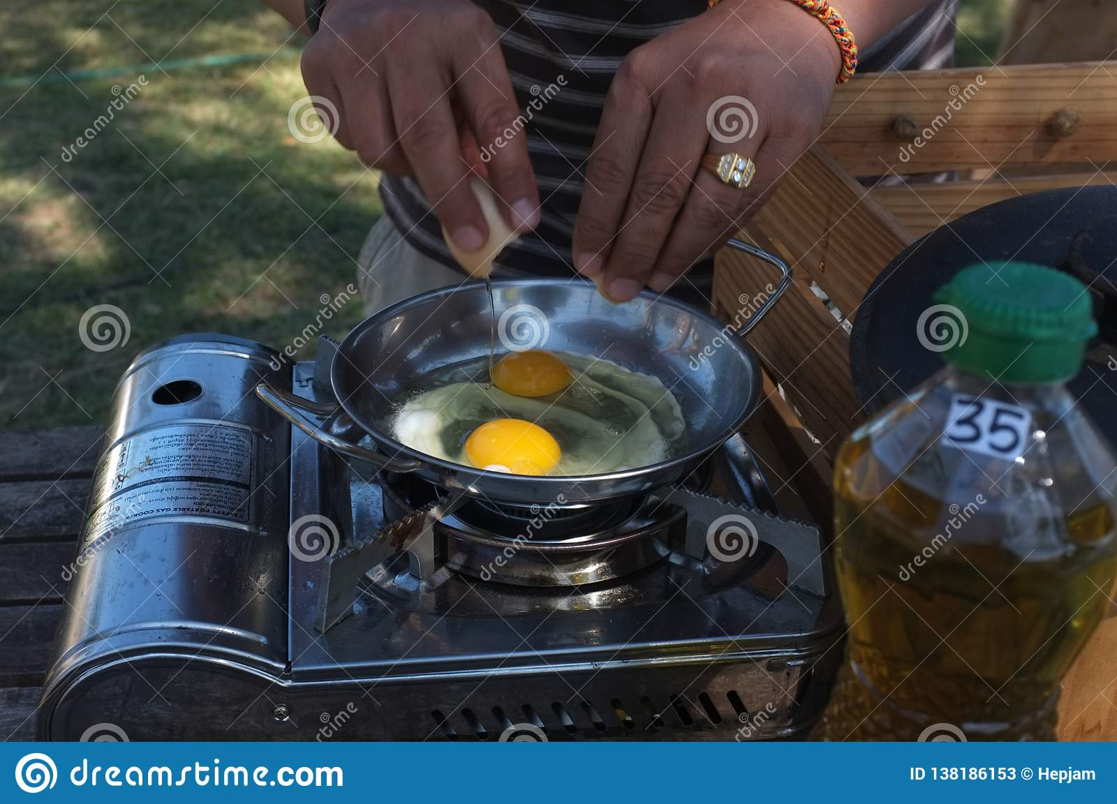 Closeup of a pair of hands cracking an egg into a pan