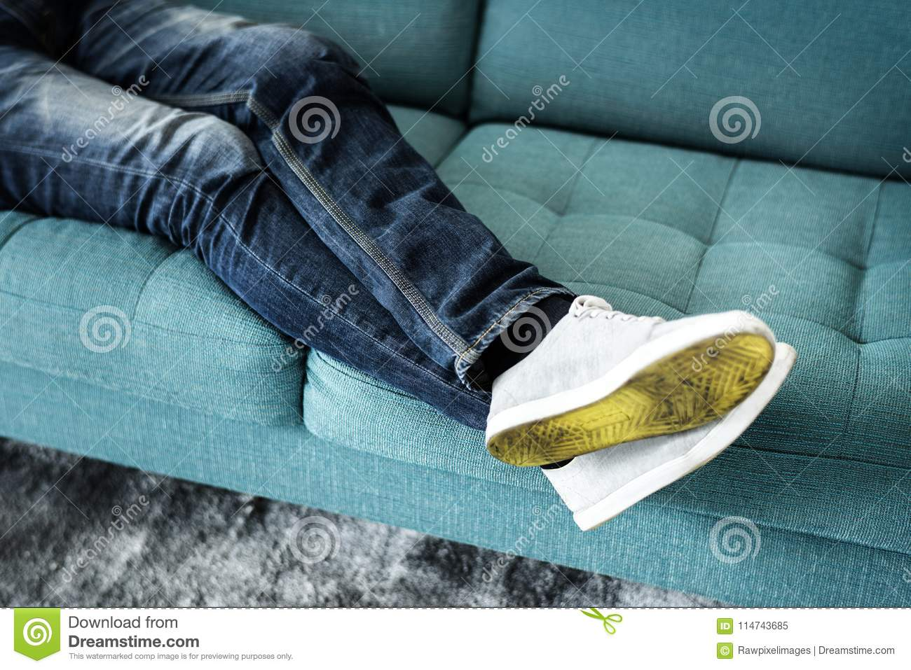 Closeup of person`s legs sitting on couch