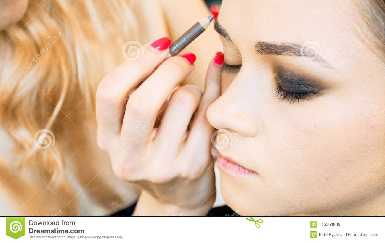 Closeup image of makeup artist painting model`s eyebrows with contouring pencil