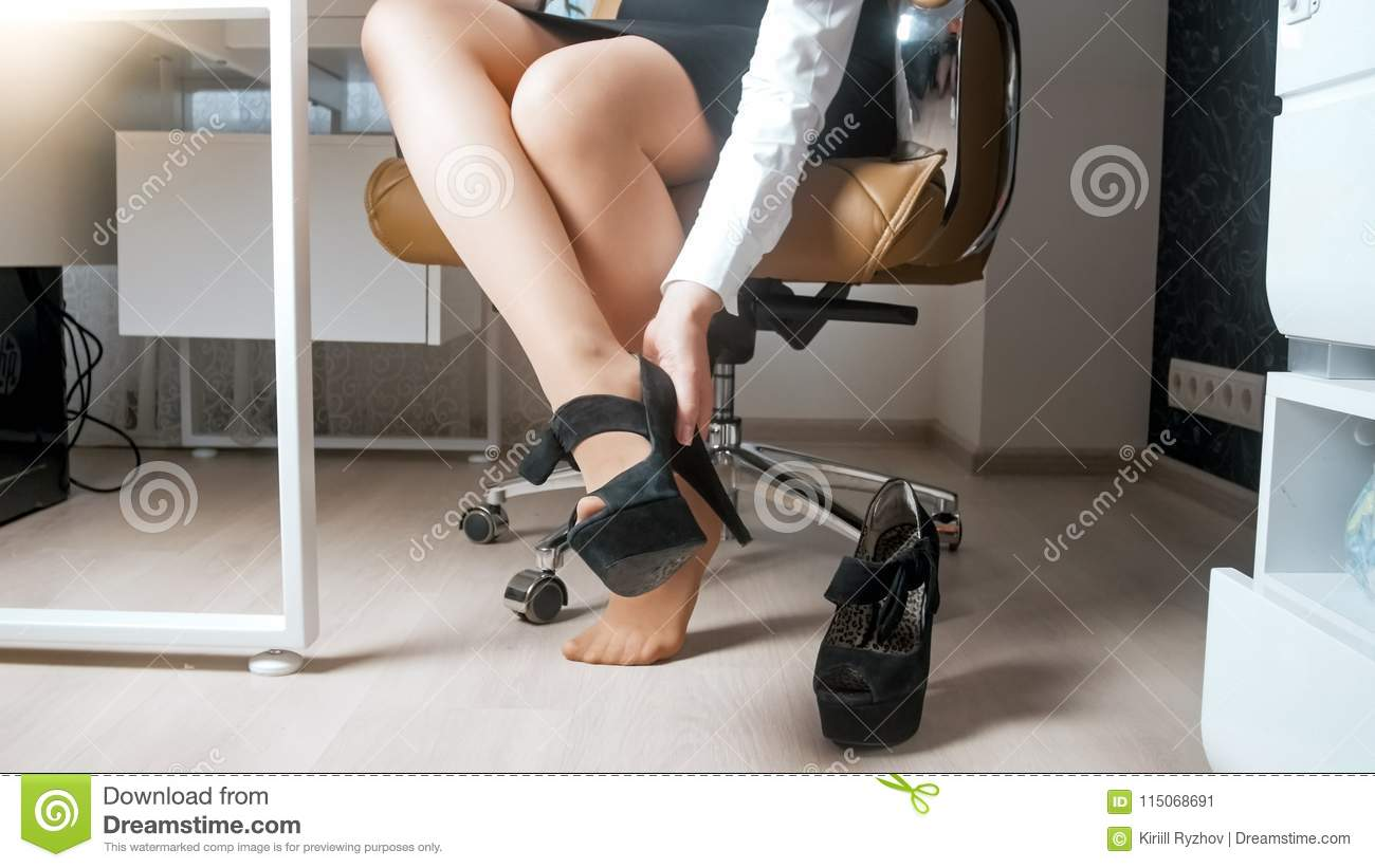 Closeup photo of young businesswoman taking off high heels shoes under table