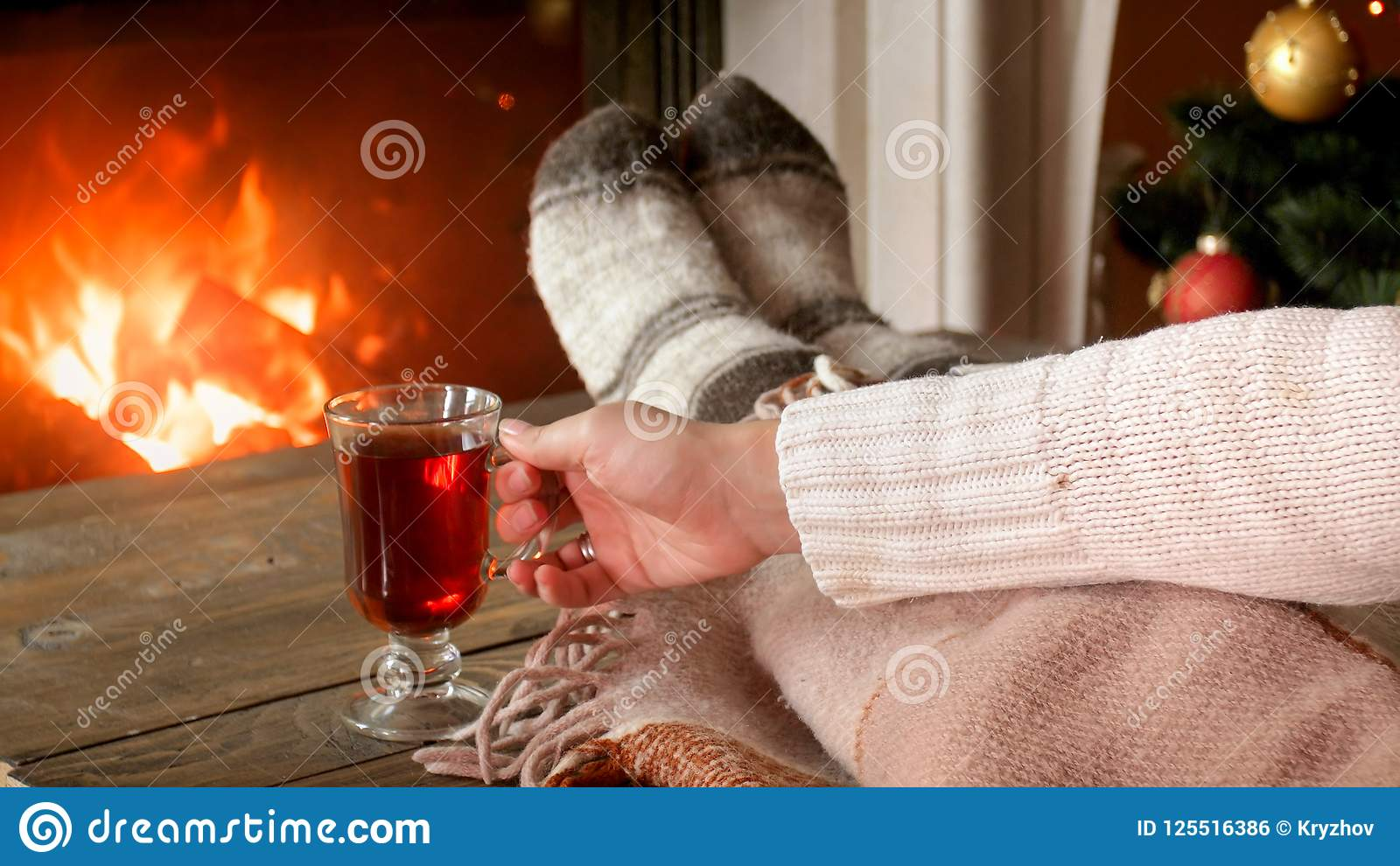 Closeup image of woman drinking mulled wine in living room y the fireplace