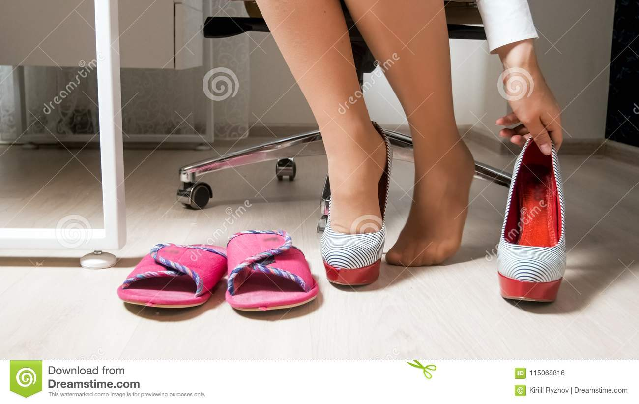 f3d4eed9f Closeup image of young businesswoman in pantyhose taking high heels shoes  and wearing comfortable home slippers