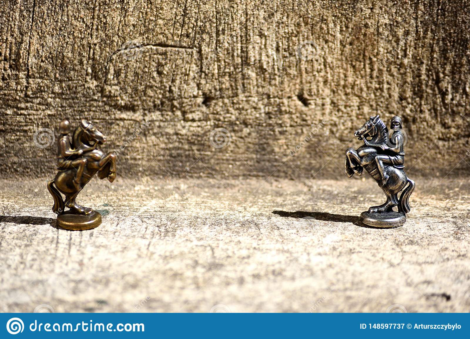 Closeup Picture of Two Bronze Chess Pieces Knights Chessmen Set beside Facing Each Other One in Focus Another Defocused