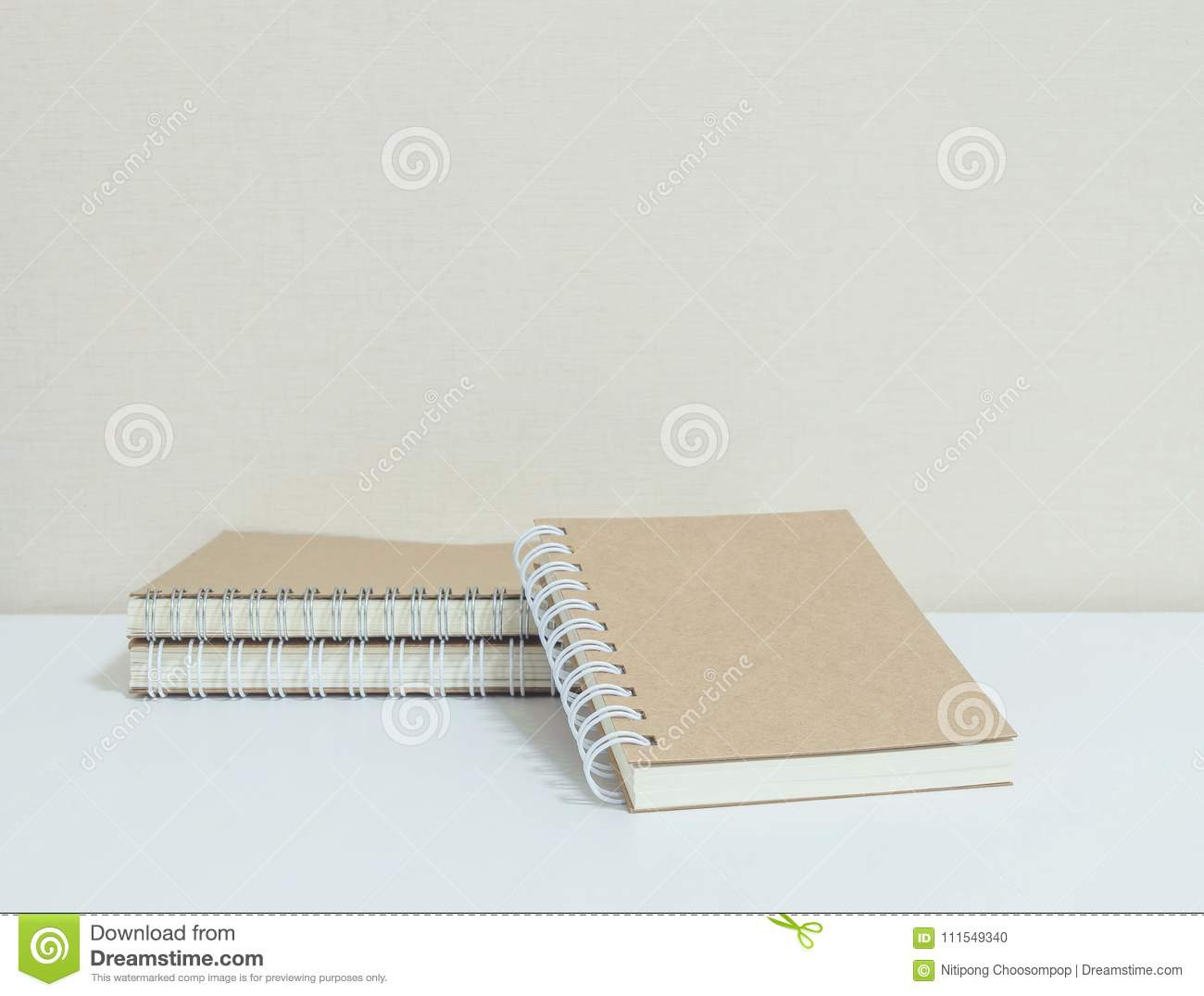 Closeup pile of brown note book on white desk and wallpaper in room textured background with copy space