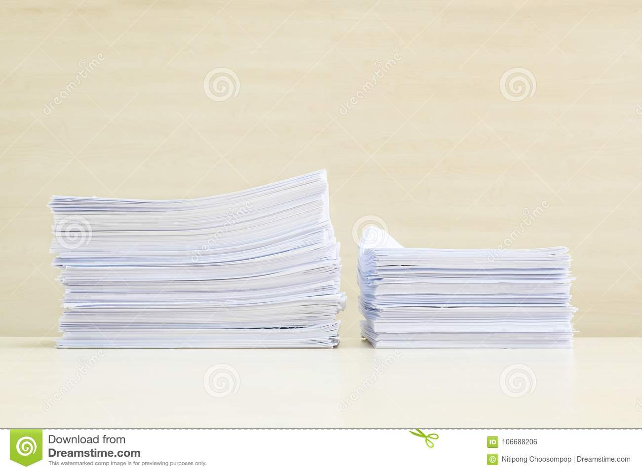 Closeup pile of work paper on blurred wooden desk and wall textured background in the meeting room under window light , hard work
