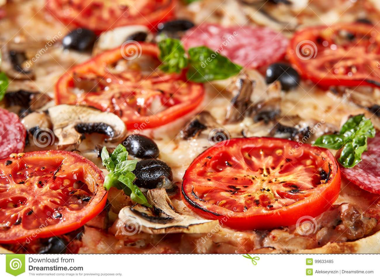 Closeup of pizza with salami, tomatoes and olives