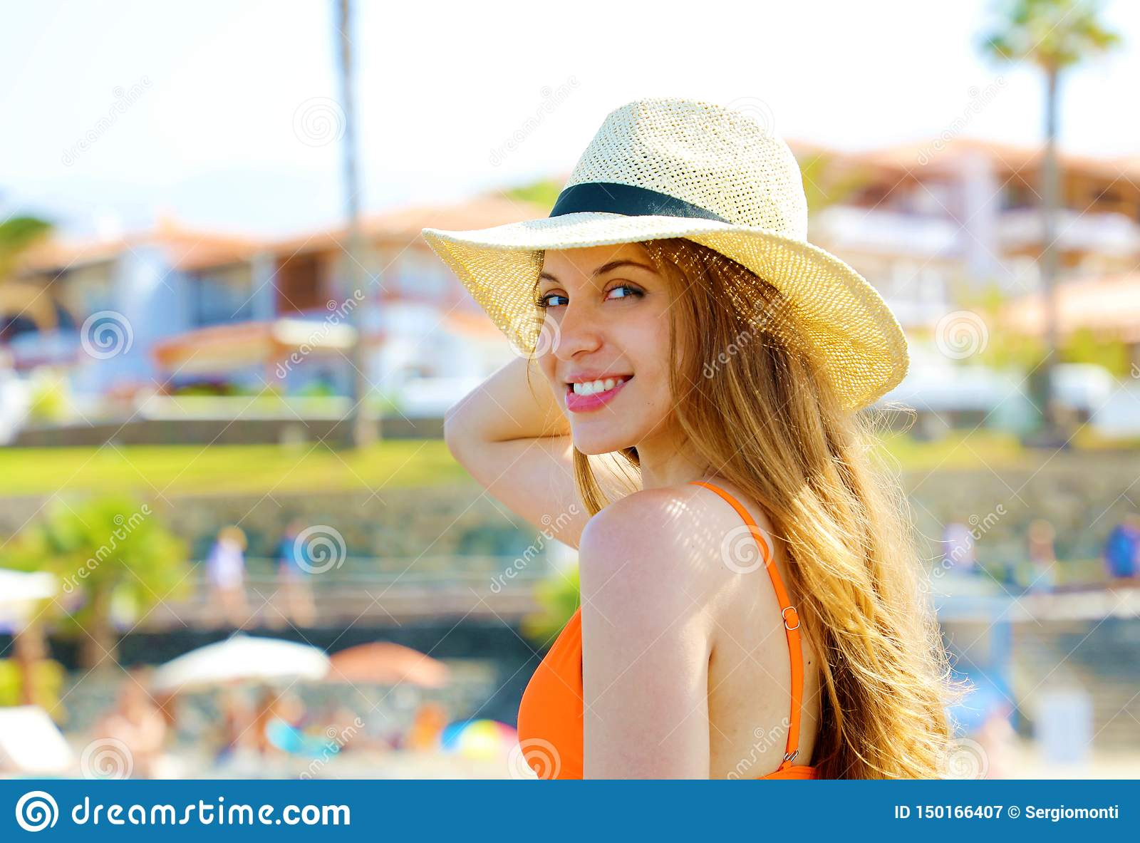 Closeup portrait of attractive blonde girl with long hair and hat posing on the beach. Beautiful bikini woman smiles to the camera