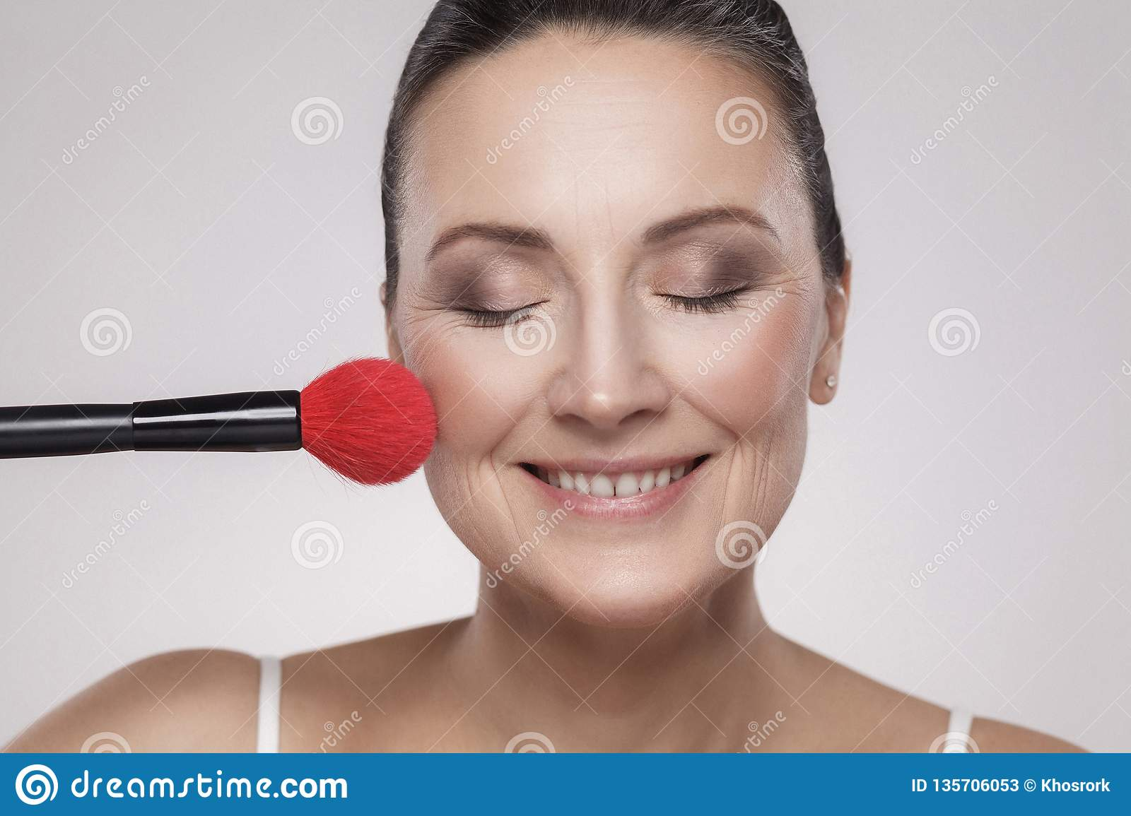 Closeup portrait of a attractive middle aged woman with perfect skin applying makeup with a red