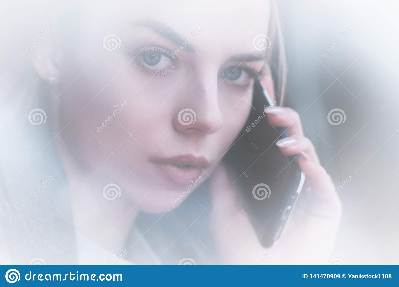 Closeup portrait attractive young girl talking on the phone look at camera. Non-contrast view through the reflection of