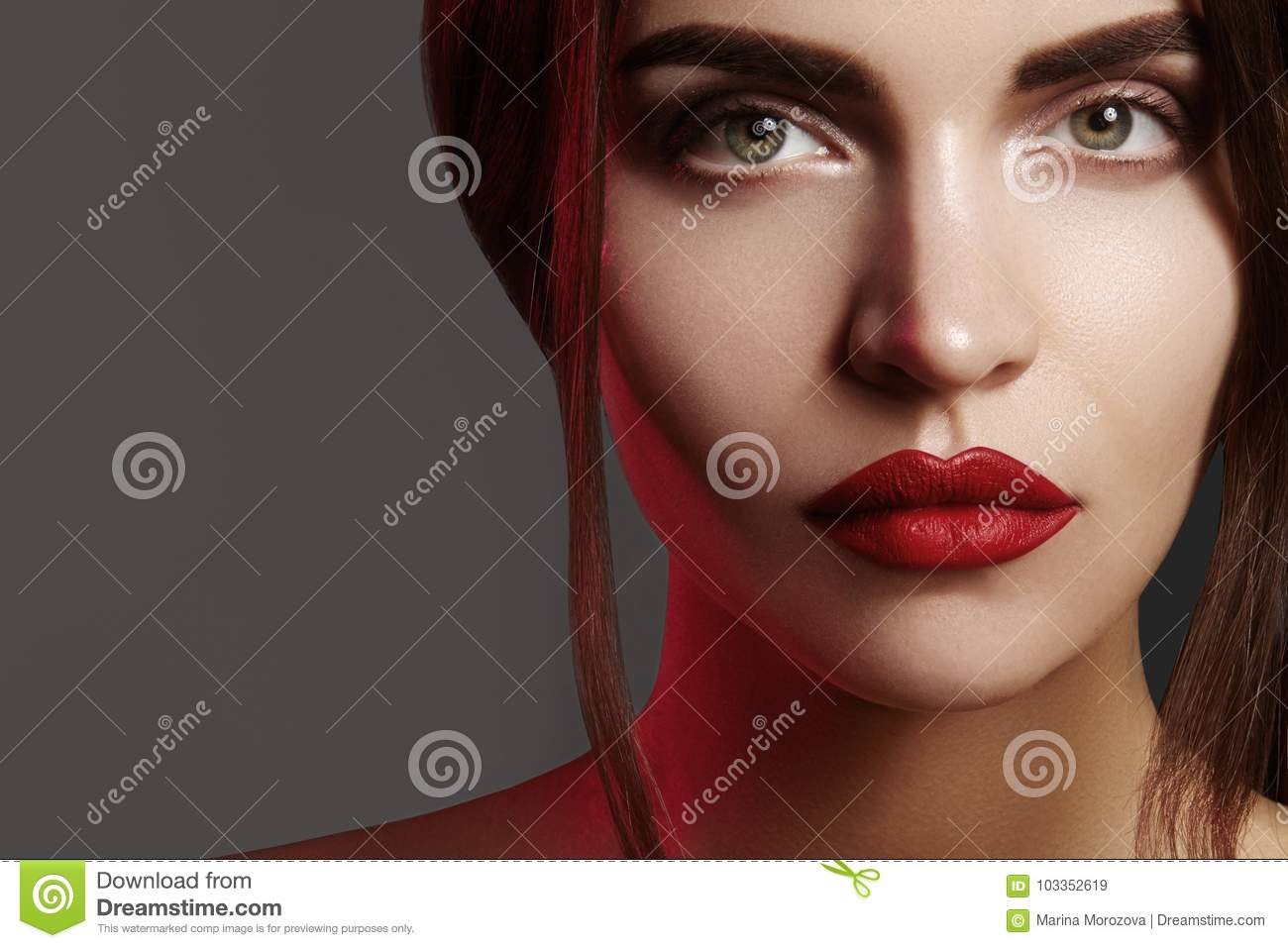 Closeup portrait with of beautiful woman face. Red color of fashion lip makeup, clean shiny skin and strong eyebrows