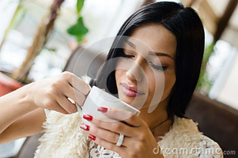 Closeup portrait of drinking coffee or tea beautiful brunette girl young woman having fun gently smiling eyes closed
