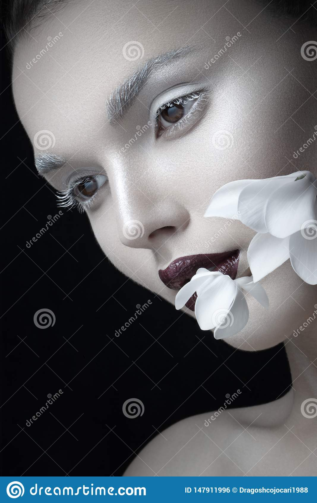 Close Up portrait of fashion, make up artistic and burgundy lips, near face flower, isolated on a black background.