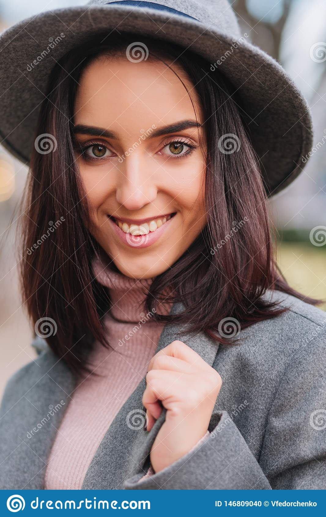 Closeup portrait fashionable charming young woman with brunette hair, in grey hat smiling to camera on street in city