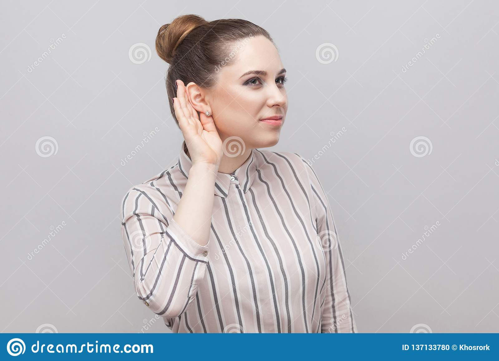 Closeup portrait of funny beautiful young woman in striped shirt and brown collected ban hairstyle, standing with hand near ear