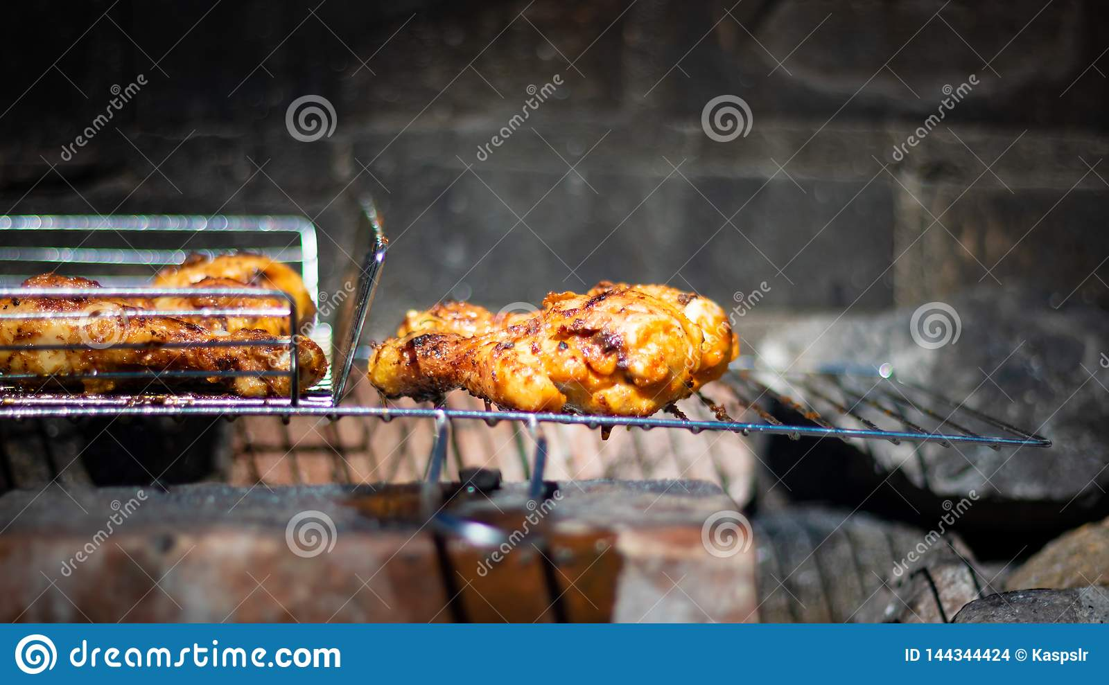 Closeup portrait of grilled chicken leg in natural coal grill