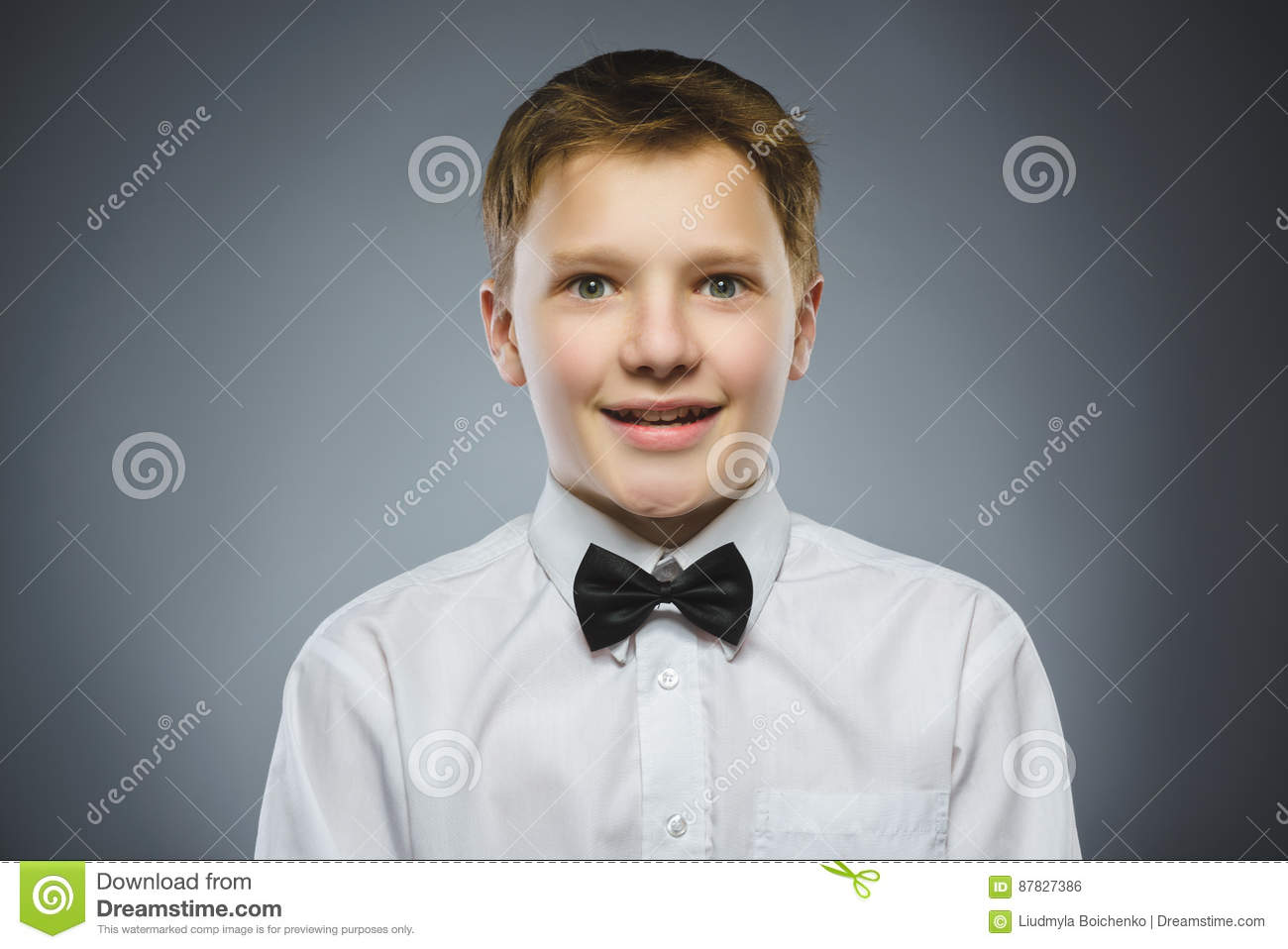 Closeup Portrait of handsome boy with astonished expression on grey background