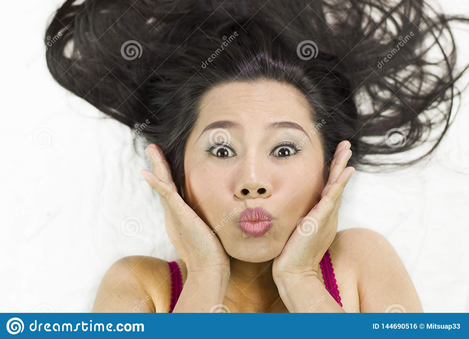Closeup portrait of happy asian women  lying on ground with black long hair. acting smile, fun