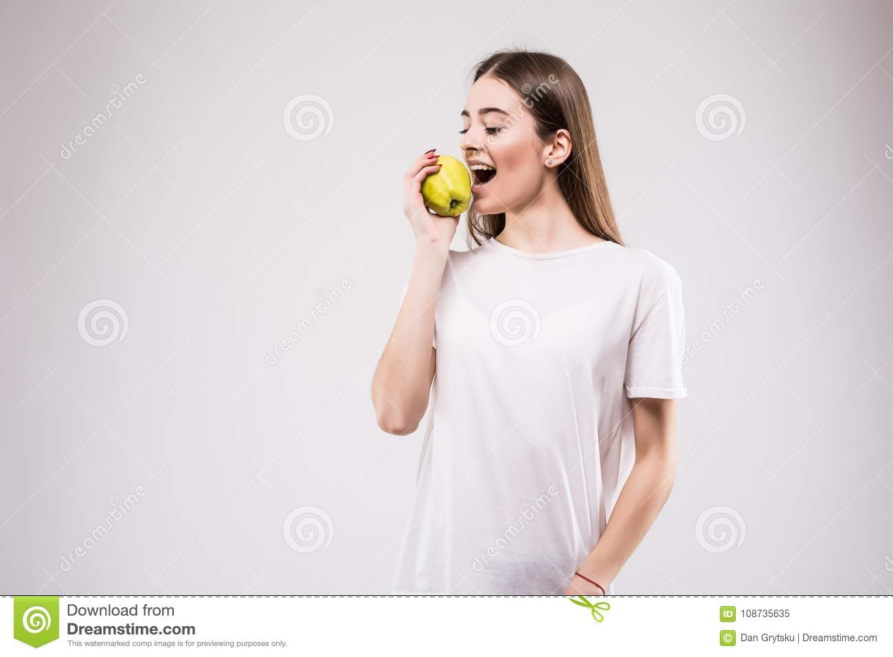 Closeup portrait of lovely young brunette woman biting juicy fresh delicious apple against gray background. Beautiful young lady e