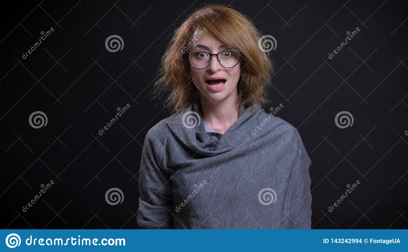 Closeup portrait of middle-aged extravagant redhead female in glasses getting surprised and excited while looking