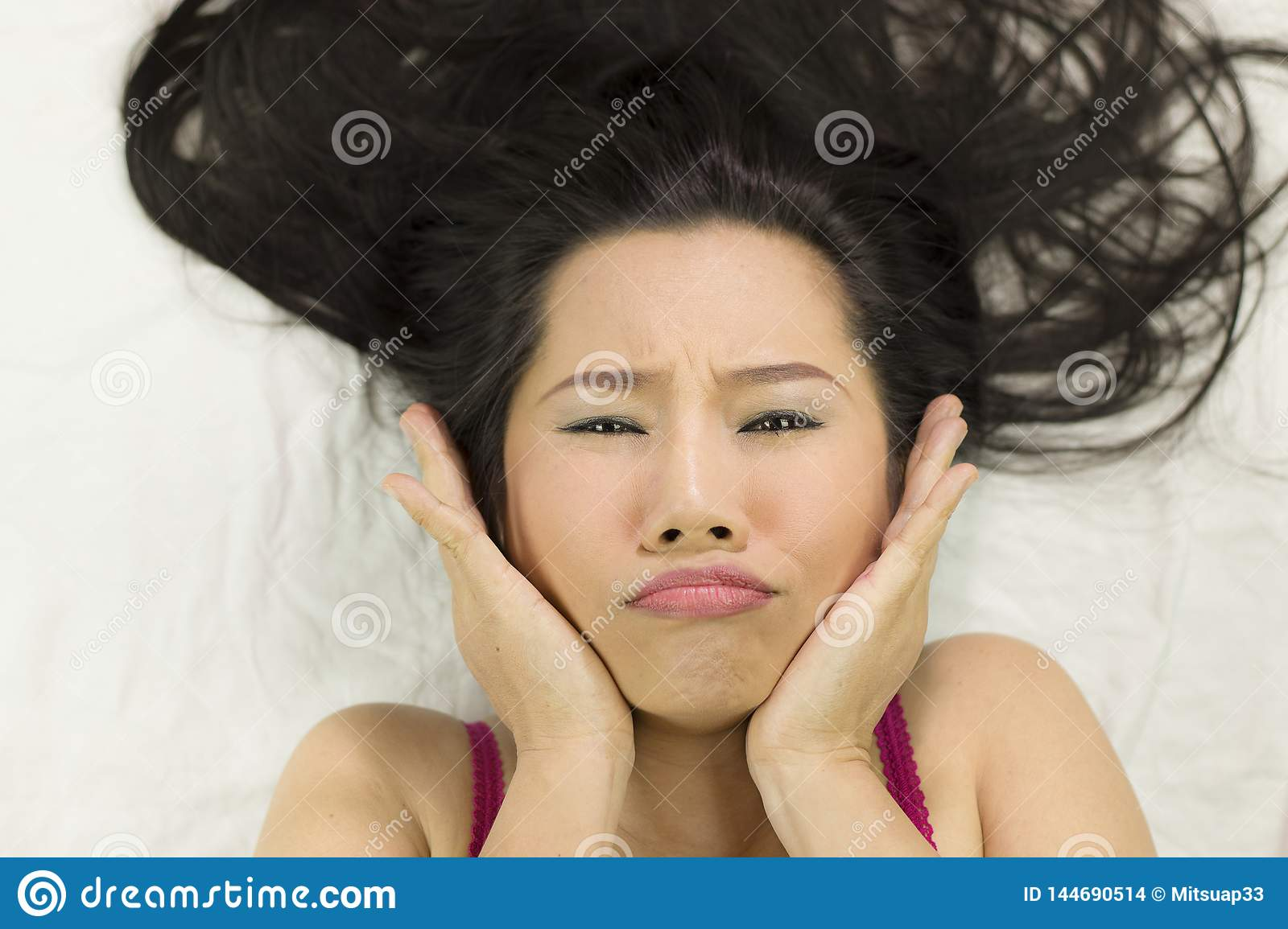 Closeup portrait of moody asian women  lying on ground with black long hair. acting upset , unhappy