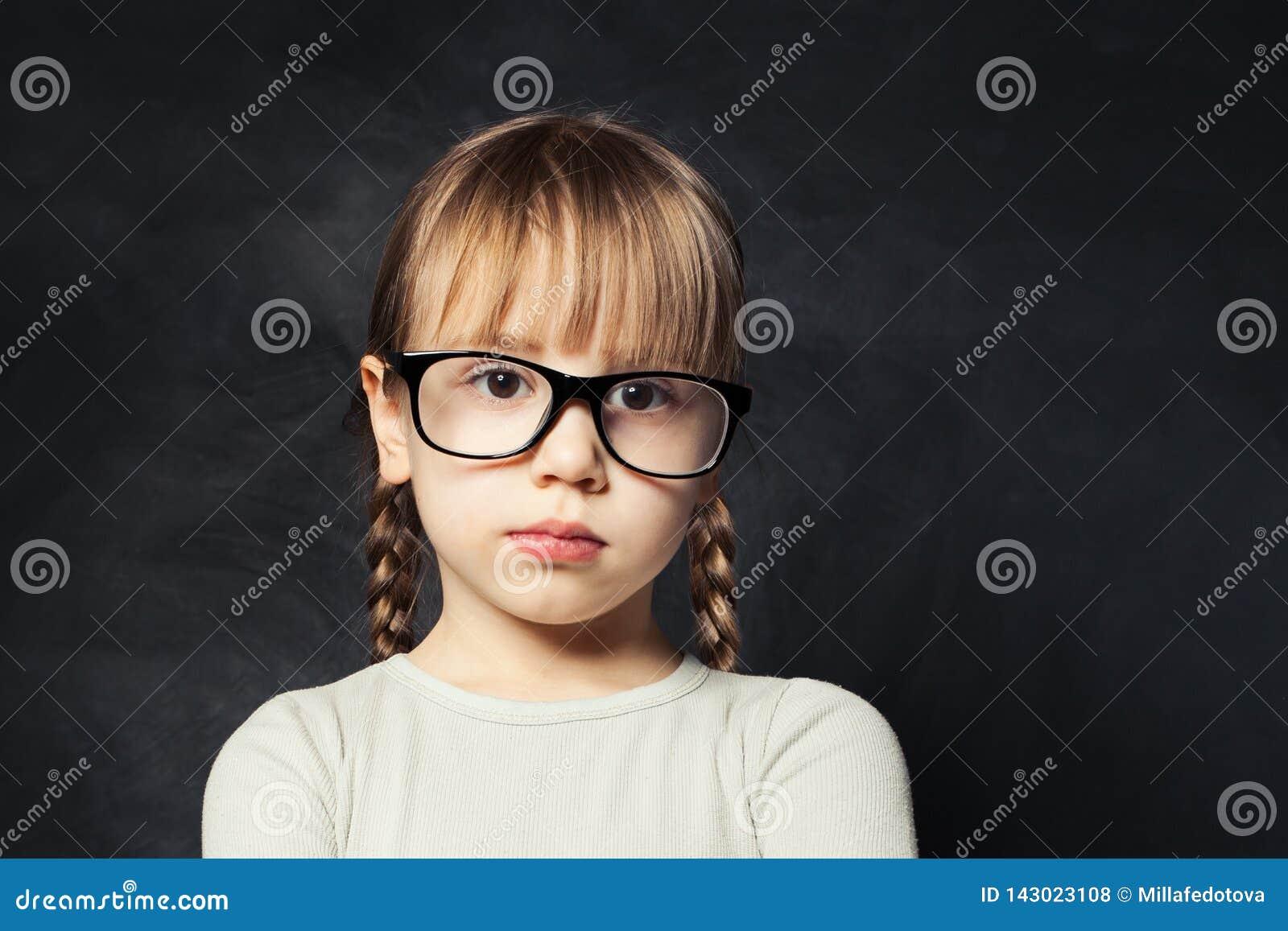 Closeup portrait of pensive child. Cute kid girl on school classroom background