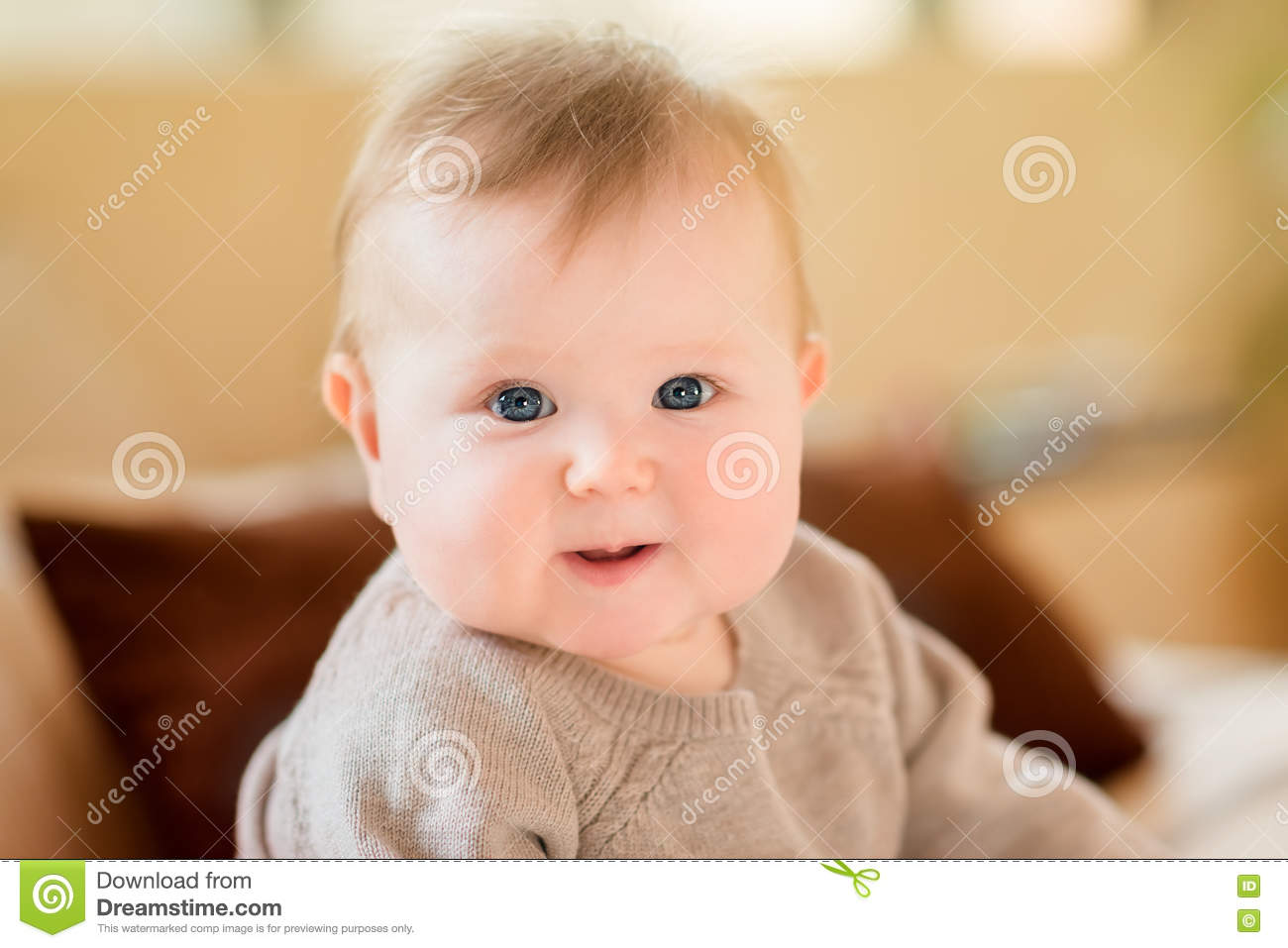 Closeup portrait of smiling little child with blond hair and blue eyes wearing knitted sweater sitting on sofa