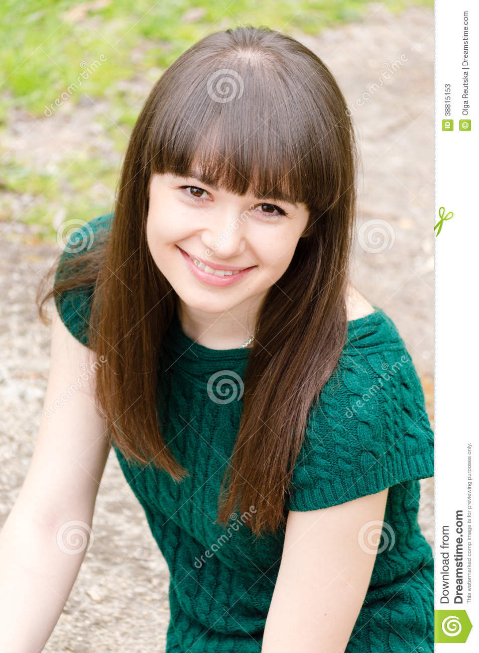 Closeup portrait of young beautiful woman brunette girl sitting outdoors happy smiling & looking at camera
